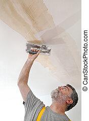 Worker repairing plaster at ceiling - Worker spreading ...