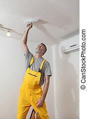 Worker repairing plaster at ceiling