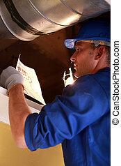 Worker repairing ventilation system