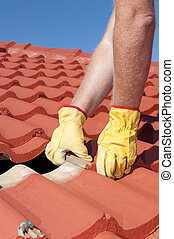 Worker replacing roof tiles on house