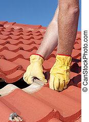Worker replacing roof tiles on house - Roof repair, worker...