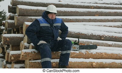 Worker resting on big pile of logs in winter forest