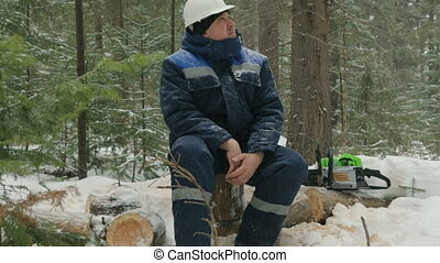 Worker resting on log in winter forest
