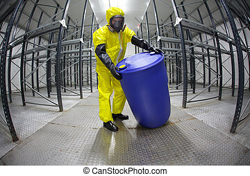 Worker in protective uniform, mask, gloves and boots rolling barrel of chemicals in empty storehouse - fish eye lens