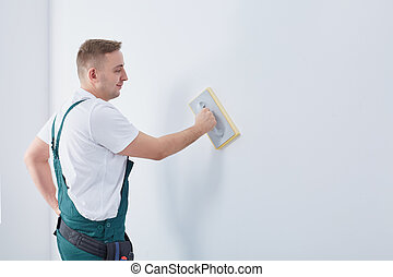Worker rubbing the wall down
