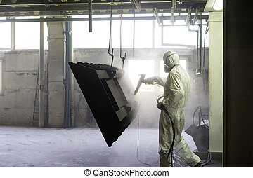 worker sand blasting a metal crate