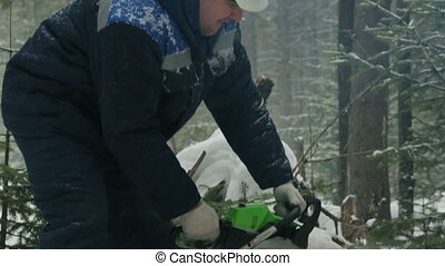 Worker sawing with chainsaw in winter forest