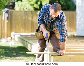Worker Sawing Wood At Construction Site