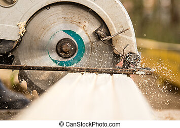 worker saws a wooden plank at a construction site