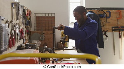 Side view of an African American male worker in a workshop at a factory making wheelchairs, standing at a workbench using a hand tool and assembling parts of a product and checking it, with tools beside him and hanging on the wall in front of him