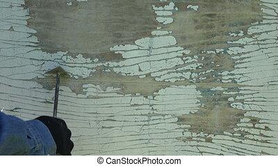 Worker scrubbing off peeling paint, 4K - Worker hand wearing...