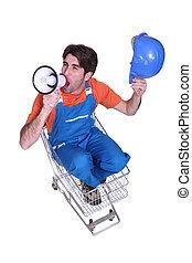 worker seated in cart shouting in loudspeaker