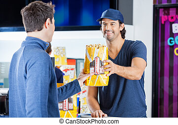Worker Selling Popcorn To Man At Concession Stand