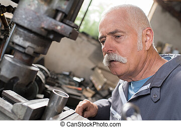 worker serves a cnc milling machine in mechanical engineering