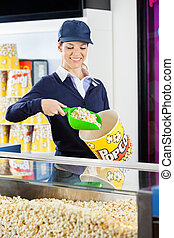 Worker Serving Popcorn In Bucket At Cinema Concession Counter