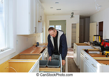 Worker installing kitchen cupboard installation of kitchen. worker ...