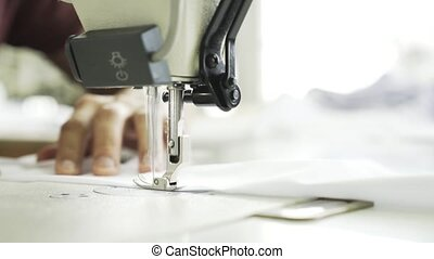 Worker sewing a white shirt at a factory