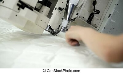 Worker sews cloth on mattress in factory indoors. Keeps by...
