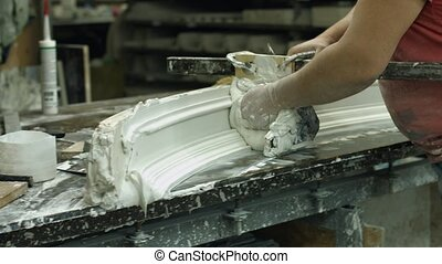 Worker shaping gypsum product. Craftsman works with gypsum...