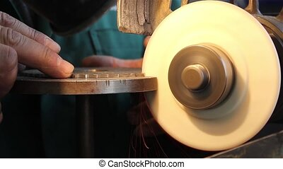 Worker sharpens a circular saw blade - The work deals with...