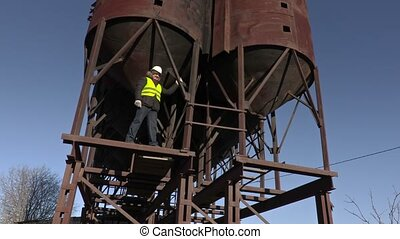 Worker show thumb up on metal tanks