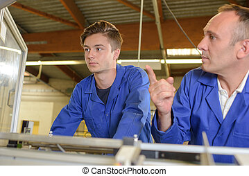 Worker showing a machine to his apprentice