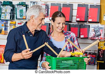 Worker Showing Folding Ruler To Customer In Hardware Shop