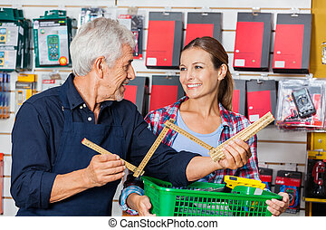 Worker Showing Folding Ruler To Customer In Hardware Store