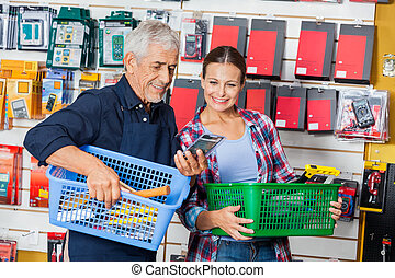 Worker Showing Product To Customer In Hardware Shop