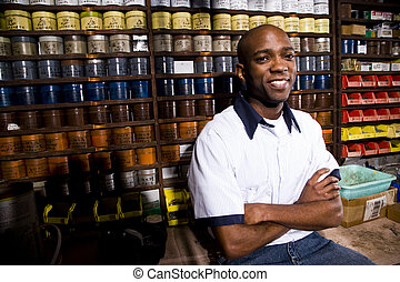 Worker sitting in front of colored inks in print shop