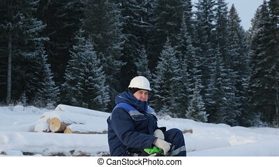 Worker sitting on pile of logs in the forest