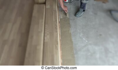 Worker smears glue on concrete floor in new apartment....