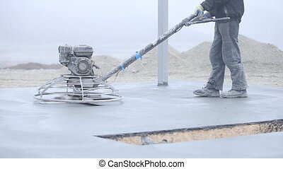 Worker smoothes concrete surface