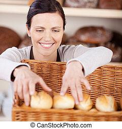 Worker sorting fresh rolls in a bakery