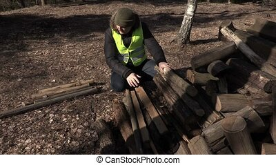 Worker sorting logs in autumn day