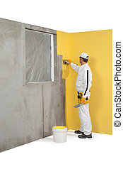 Worker spreading a plaster on a corner-wall
