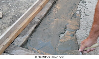 Worker spreading mortar or tile adhesive to concrete using...