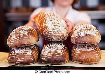 Worker stacking bread in a bakery - Female worker stacking...