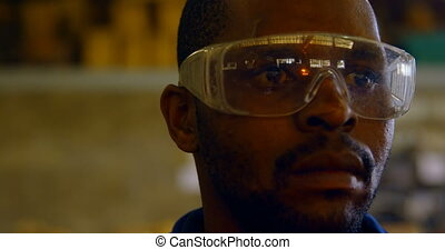 Worker standing in protective eyewear in foundry workshop 4k...
