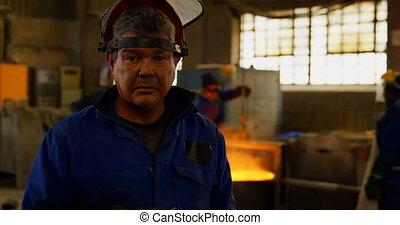 Worker standing in protective helmet in foundry workshop 4k...
