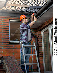 Worker standing on step ladder and repairing gutter on house...