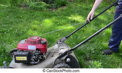 worker start grass mower - man gardener worker start grass...