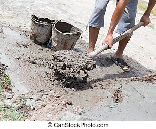 Worker stirs concrete shovel