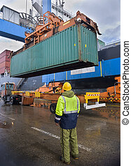 worker supervising container uploading at dock