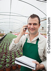 Worker taking notes and calling in greenhouse