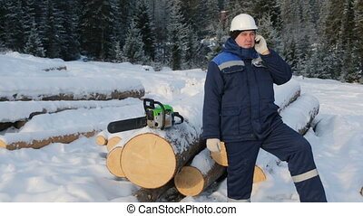 Worker talking on cellphone near pile of logs in the forest