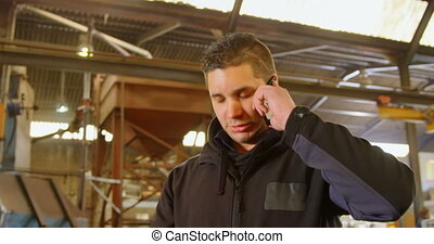 Worker talking on mobile phone in foundry workshop 4k - ...