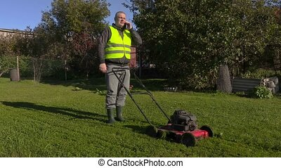 Worker talking on phone and pushing lawn mower