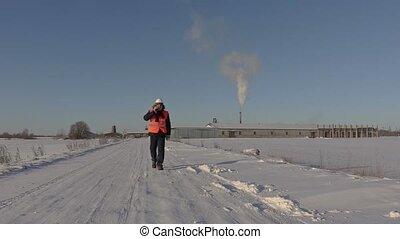 Worker talking on phone near factory