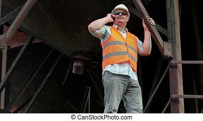 Worker talking on smart phone in fa